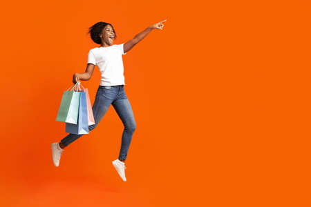 Excited african american young woman with colorful shopping bags jumping in the air and pointing at copy space for sales or discounts advertisement, orange studio background, panorama