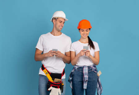 Young Couple In Protective Helmets Using Smartphones Over Blue Background, Shopping Construction Tools Online, Man And Woman Counting Repair Budget Or Browsing House Remodelling App, Copy Space