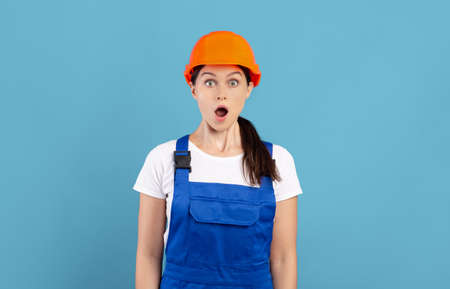 Portrait Of Shocked Handywoman In Hardhat And Coveralls Standing Over Blue Background, Surprised Female Repair Worker Posing With Open Mouth, Emotionally Reacting To Renovation News, Copy Space Banque d'images