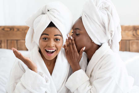 Closeup of two emotional african american women having spa day at home, wearing bathrobes, sitting on bed and sharing secrets. Black woman whispering secrets to her amazed bestie, bedroom interior