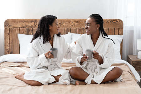 Positive black girlfriends in bathrobes sitting on bed at home, talking and drinking coffee. Two happy african american women spending day at hotel, resting after treatment, drinking tea, copy space