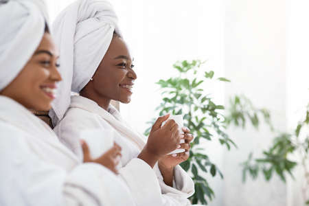 Closeup of black cheerful girlfriends in bathrobes and towels on their heads holding mugs of herbal tea looking at copy space, panorama. African american young women having beauty day at home