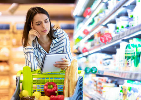 Pensive Woman Holding Grocery Shopping Checklist, Looking In Notebook, Reading Notes, Buying Products, Standing With Trolley Cart In Supermarket. Young Millennial Lady Thinking About Purchase
