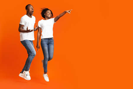 Excited african-american couple jumping up and cheerfully pointing away at empty space, orange studio background. Emotional young black man and woman aiming at advertisement, full length photo