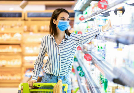 Consumerism And Consumption. Female customer in disposable face mask choosing dairy products, holding bottle of milk or yoghurt. Woman standing with shopping trolley near the fridge in mall Banque d'images
