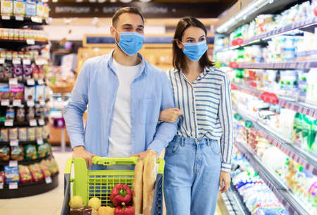 Family At Shop. Smiling Young Couple In Protective Surgical Masks Shopping Groceries In The Supermarket, Cheerful Customers Walking With Full Trolley Cart In Store Interior, Buying Food