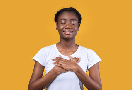Thank You. Thankful African American Young Woman Pressing Hands To Chest Standing Posing With Eyes Closed Over Yellow Studio Background. Gratitude And Kindness Concept