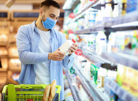 Choosing Milk. Young man in disposable medical surgical mask holding bottle of milk or yoghurt from the fridge, looking at dairy products, standing near refrigerator aisle, checking expiry date