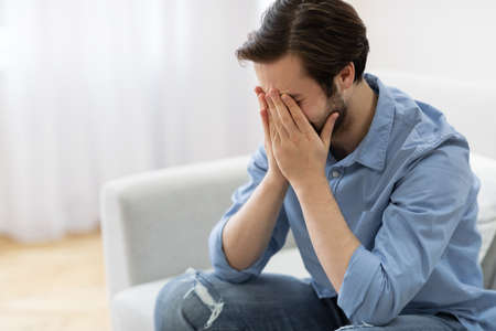 Male Depression. Frustrated Man Crying Covering Face Sitting On Sofa At Home. Desperate Guy Cries In Living Room. Unhappiness And Stressful Modern Life Concept. Empty Space For Text