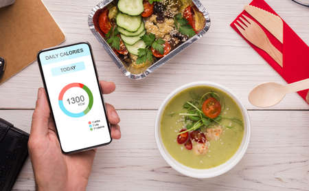 Healthy Eating. Man Using Daily Calories Counting App On Smartphone And Having Lunch At Workplace In Office, Ordered Food Delivery Service, Creative Collage For Dieting Concept, Top View