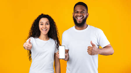 Excited Multiracial Couple Showing Phone Blank Screen Gesturing Thumbs Up In Approvement Standing Posing Over Yellow Studio Background. We Like This Mobile Application. Panorama, Mockup Banco de Imagens