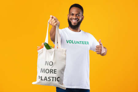 No More Plastic. Cheerful Volunteer Man Holding Eco Bag With Groceries Gesturing Thumbs Up Standing On Yellow Studio Background. Ecology And Consumerism, I Like Eco-Friendly Lifestyle Concept