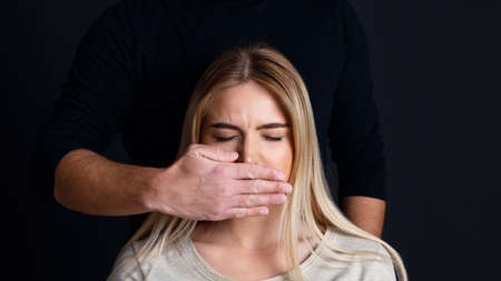 Psychological and physical pressure man on woman. Male hand closes mouth of sad woman with closed eyes, panorama, copy space