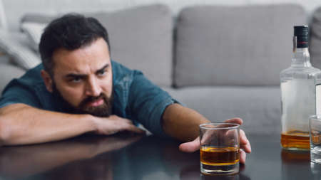 Alcoholism and problems in family. Frustrated man with beard takes a glass of whiskey from table in living room interior, panorama, copy space
