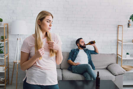 Latent alcoholism. Sad wife sees her husband drinking a lot of beer, man with beard sits on couch, near table with empty bottles
