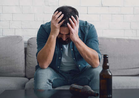 Despair and alcoholism. Sad man alcoholic holds his head with hands, empty bottles on table in interior of living room