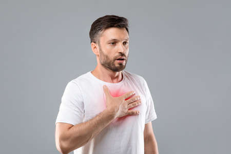 Breathing problem. Sick middle-aged man with chest pain touching inflammated zone and looking at copy space, grey studio background. Bearded man suffering from pneumonia or asthma. COVID-19 concept Standard-Bild