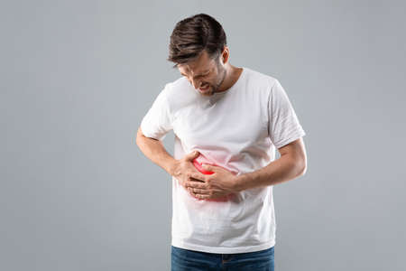 Middle-aged man holding his lightened with red right side, suffering from liver pain, grey studio background, copy space. Sad man having cirrhosis, rubbing his right side. Liver diseases concept