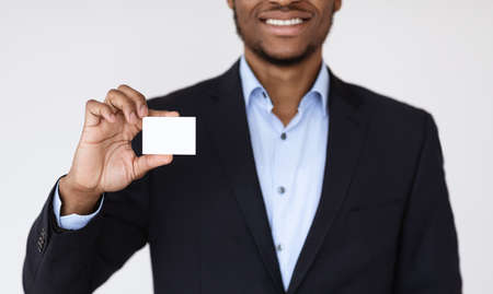 Cropped of black businessman handing blank business card on white background, panorama. Empty card in african american man hands, manager representing himself with business card, copy space Stock Photo