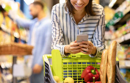 Couple In The Supermarket. Cropped closeup image of unrecognizable smiling woman leaning on shopping cart, using mobile phone, her boyfriend is choosing food in the blurred background