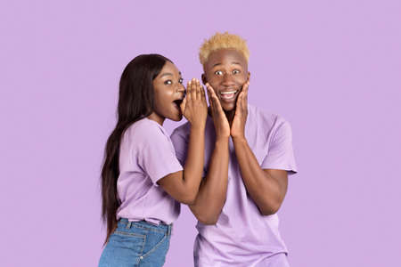 Excited black woman whispering something into her boyfriends ear over lilac studio background. Positive African American couple gossiping, sharing big secret with each other