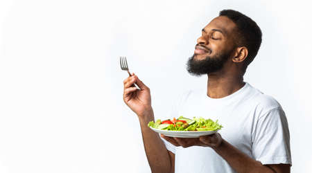 Bearded Black Guy Enjoying Delicious Vegetable Salad Standing With Plate Over White Studio Background. Healthy Nutrition, Dinner Delivery Concept. Side View, Panorama With Copy Space Standard-Bild