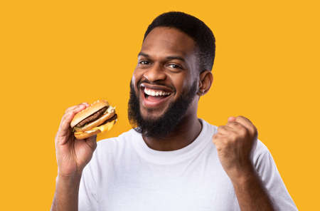Joyful Black Guy Holding Burger Gesturing Yes Eating Unhealthy Fast Food Standing Over Yellow Studio Background, Smiling To Camera. Junk Food Lover. Finally Cheat Meal Concept