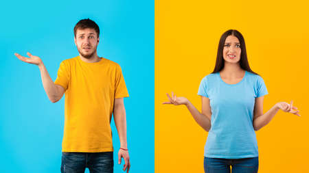 Who Knows. Portrait Of Funny Confused Man And Woman Shrugging Shoulders, Looking At Camera Posing Over Blue And Yellow Halved Background. Studio Shot. Puzzled couple is clueless. Im sorry