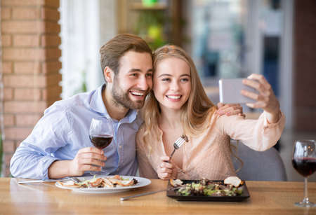 Positive young couple eating lunch together at restaurant, talking selfie during meal. Attractive millennial guy with his lovely girlfriend on romantic date, making memories and having fun