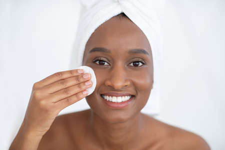 Youth, beauty and glowing skin, home care and spa. Millennial african american woman with towel, cleanser face with cotton pad, tonic after shower and looks at camera as mirror, on white background Banque d'images