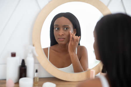 First signs of aging, problem skin and beauty care. Alarmed millennial african american lady looks on her face in mirror and fights with pimples and wrinkles in bedroom interior in morning, copy space 版權商用圖片