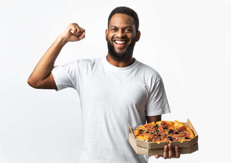 African American Guy Posing With Pizza Box Showing Biceps Smiling To Camera Standing Over White Studio Background. Junk Food Eater, Male Nutrition And Cheat Meal Concept