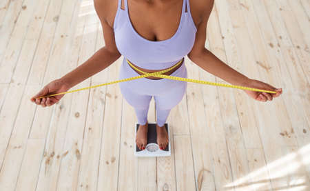 Closeup of slim black woman measuring her waist while standing on scales at home, above view. African American lady checking result of her weight loss diet. Healthy nutrition concept