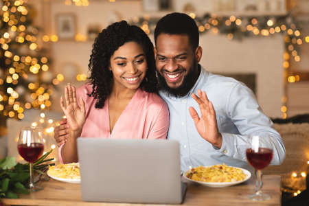 Virtual Party. Black couple sitting at the table, having dinner, drinking wine and having video call with parents or friends on laptop, waving to webcam. Stay home, quarantine celebration of event