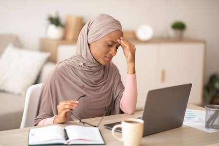 Deadline stress. Exhausted black woman in hijab tired after working on laptop for too long, having headache at home. Young Muslim lady in traditional headscarf overworking on freelance job