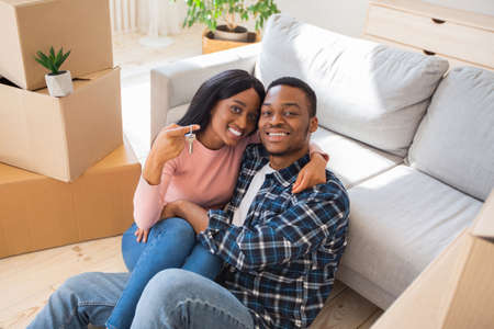 Black millennial lady with her husband hugging and holding house key in their new property. Happy young homeowners cuddling on floor on moving day. Relocation concept