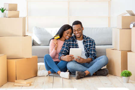 Online shopping concept. Happy black couple with tablet computer and credit card buying household goods on web. Young African American family purchasing home decor on internet
