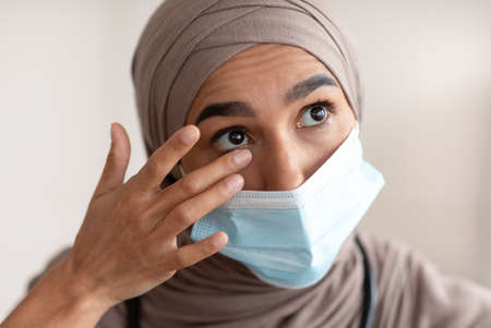 Avoid face touching, Coronavirus prevention, Doctors protection during COVID-19 pandemic. Overworked female doctor in protective face mask and hijab touching her eyes, closeup portrait Standard-Bild