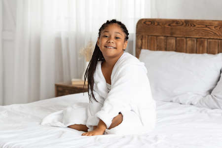 Beautiful cute little african american girl in bathrobe relaxing on bed at home after shower, cheerful black kid enjoying spa beauty treatments, smiling and looking at camera, copy space Banque d'images
