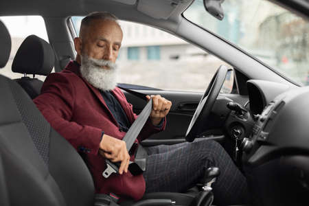 Driving safety concept. Elderly businessman fasten seat belt in his car, ready to go to office. Aged grey-haired man in stylish suit putting on his seatbelt before driving car to airport, copy space