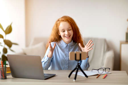 Blogging Concept. Smiling red-haired teen girl recording lifestyle blog talking to camera of mobile phone on tripod, sitting at desk at home. Happy young influencer filming vlog for her channel