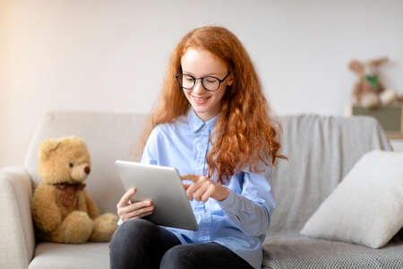 Digital Natives. Portrait of positive smiling red-haired teenage girl wearing eyeglasses sitting on the couch and using digital tablet, browsing internet, studying online, reading news