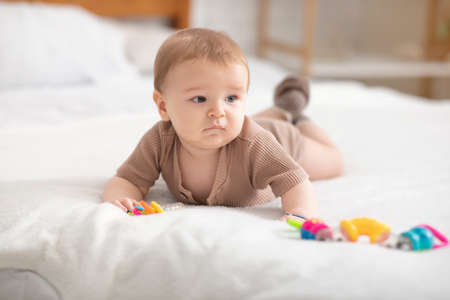 Cute little baby boy or girl playing with toys while laying on bed at home, looking at copy space. Adorable toddler having fun, lying on belly and palying with beanbag. Kids toys, maracas concept Reklamní fotografie