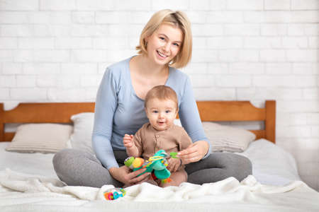 Developmental Activities for Babies. Caucasian mother hugging baby and holding toys, playing with her cute infant child, sitting on bed at home, copy space. Mom and baby having good time together Zdjęcie Seryjne