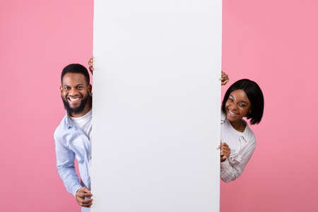 Black woman and guy holding white advertising board over pink studio background, panorama. Mockup for your design. Happy young couple showing blank poster with space for text