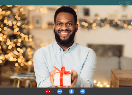 Holidays And Lockdown. Monitor view of cheerful bearded african american man making online video call, showing gift box with present to web camera. Program application interface for video conference