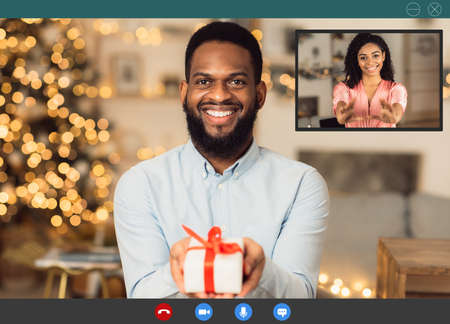 Virtual Dating During Pandemic. Monitor view of black man having digital romantic date online, showing present box with gift to his girlfriend in videochat. Program for video conference