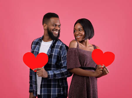 Pair of sweethearts with red hearts looking at each other with love, celebrating Valentines Day on pink studio background. Beautiful black couple spending romantic times together