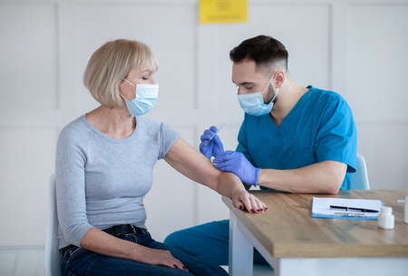 Senior lady being vaccinated against coronavirus at clinic, participating in antiviral campaign. Mature woman getting covid-19 vaccine injection at medical office. Infectious disease treatment concept
