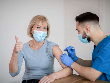 Mature woman in face mask approving of covid-19 vaccination, showing thumb up gesture during coronavirus vaccine injection at clinic. Male doctor immunizing senior patient against viral disease
